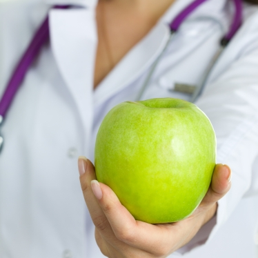 Close up view of medical doctor hand offering green apple